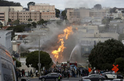 (AP Photo/Jeff Chiu). San Francisco firefighters battle a fire on Geary Boulevard in San Francisco, Wednesday, Feb. 6, 2019. A gas explosion in a San Francisco neighborhood shot flames high into the air Wednesday and was burning four buildings as utili...