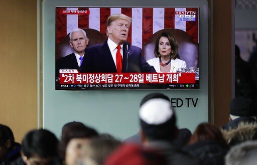 """(AP Photo/Lee Jin-man). In this Feb. 6, 2019 photo, People watch a TV screen showing a live broadcast of U.S. President Donald Trump delivering his State of the Union address at the Seoul Railway Station in Seoul, South Korea. The letters read """" The se..."""