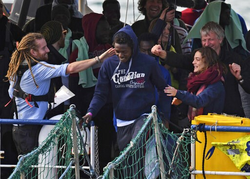 (AP Photo/Salvatore Cavalli). A migrant is cheered along as he disembarks from the rescue ship Sea-Watch 3, which was carrying 47 migrants, as it docked at the Sicilian port of Catania, southern Italy, Thursday, Jan. 31, 2019. Europe's latest migrant s...