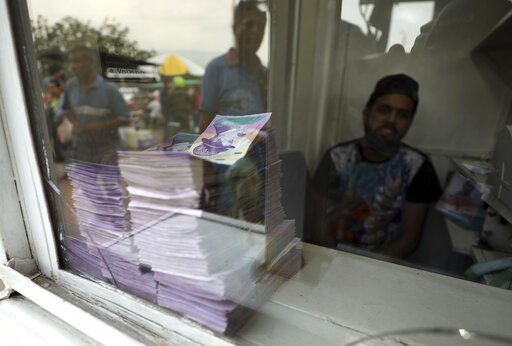 (AP Photo/Fernando Vergara). Bills of Venezuelan currency can be seen stacked at a currency exchange booth in La Parada, on the outskirts of Cucuta, Colombia, on the border with Venezuela, Wednesday, Feb. 6, 2019. Tensions in the area have risen since ...