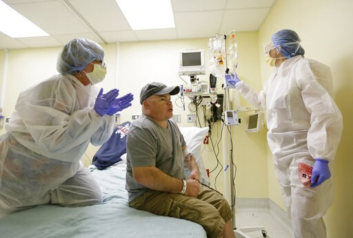 (AP Photo/Eric Risberg). FILE - In this Monday, Nov. 13, 2017 file photo, Brian Madeux, starts to receive the first human gene editing therapy for Hunter syndrome, as his girlfriend, Marcie Humphrey, left, applauds at the UCSF Benioff Children's Hospit...