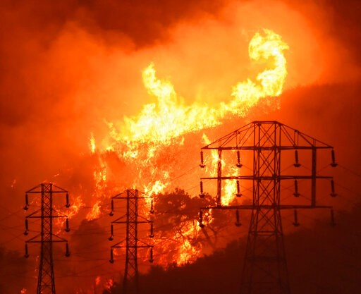 (Mike Eliason/Santa Barbara County Fire Department via AP, File). FILE - In this Dec. 16, 2017, file photo provided by the Santa Barbara County Fire Department, flames burn near power lines in Sycamore Canyon near West Mountain Drive in Montecito, Cali...