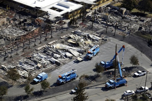 (AP Photo/Marcio Jose Sanchez, File). FILE - In this Oct. 14, 2017, file photo, crews of Pacific Gas & Electric Corp. work on restoring power lines in a fire ravaged neighborhood in an aerial view in the aftermath of a wildfire in Santa Rosa, Calif...
