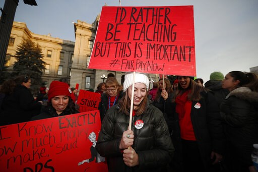 (AP Photo/David Zalubowski, File). FILE- In this Wednesday, Jan. 30, 2019 file photo, Margaret Flynn, front, a 7th-grade teacher in Denver Public Schools, leads other teachers in a march during a rally outside the state Capitol in Denver. Denver teache...