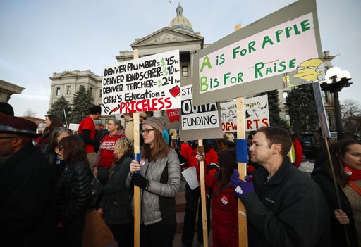 (AP Photo/David Zalubowski, File). FILE - In this Jan. 30, 2019, file photo, Denver Public Schools teachers carry placards as they wait to march after a rally in support of a strike outside the State Capitol in Denver. Teachers plan to strike next week...