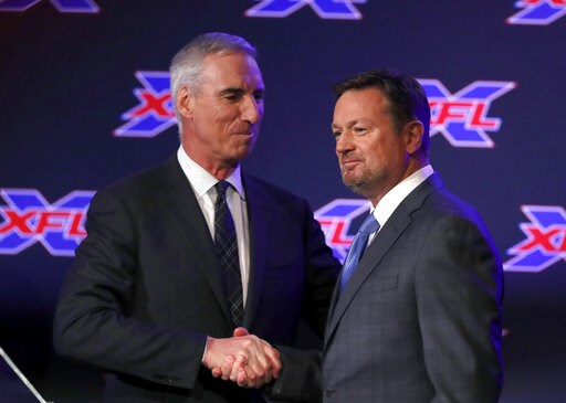 (AP Photo/Tony Gutierrez). Oliver Luck, XFL commissioner and CEO, greets Bob Stoops after introducing Stoops during a news conference as the new general manager and head coach of the Dallas XFL football team in Arlington, Texas, Thursday, Feb. 7, 2019.