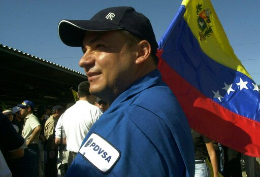 (AP Photo/Ana Maria Otero, File). FILE - In this Dec. 9, 2002 file photo, a striking oil worker holds a Venezuelan flag as he protests with other strikers outside administrative offices of Petroleos de Venezuela, SA, or PDVSA, in Maracaibo in western V...