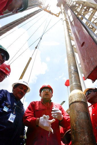 (AP Photo, File). FILE - In this Aug. 10, 2006 file photo, Venezuela's late President Hugo Chavez visits oil workers on the platform of an oil drill at Carabobo block one in the Orinoco oil belt in Venezuela's Anzoategui state. Venezuela was once one o...