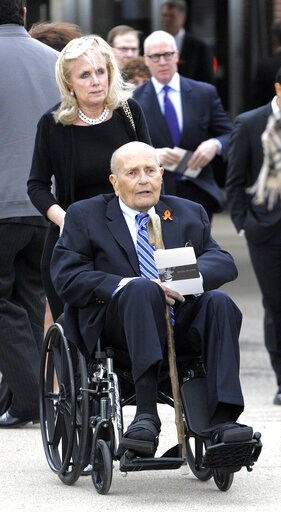 (Todd McInturf/Detroit News via AP, File). FILE - In this April 21, 2015 file photo, U.S. Rep. Debbie Dingell pushes the wheelchair of her husband, retired Congressman John Dingell after the funeral of Detroit-area businessman and philanthropist A. Alf...