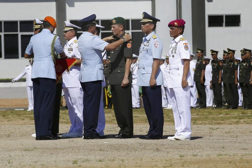 (AP Photo/Tatan Syuflana). In this May 11, 2018, photo, Indonesia Armed Forces Chief Air Marshall Hadi Tjahjanto, second left, puts on an epaulet on the shoulders of a military general during their inauguration to their new position in Sorong, Papua pr...