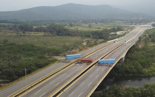 (AP Photo). This Feb. 6, 2019 image taken from video, shows a fuel tanker, cargo trailers and makeshift fencing, blocking the Tienditas International Bridge in an attempt to stop humanitarian aid entering from Colombia, as seen from the outskirts of Cu...