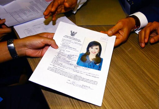 (AP Photo). Leader of Thai Raksa Chart party Preecha Pholphongpanich, right, hands a paper with a picture of Princess Ubolratana at election commission of Thailand in Bangkok, Thailand, Friday, Feb. 8, 2019. The political party has selected the princes...