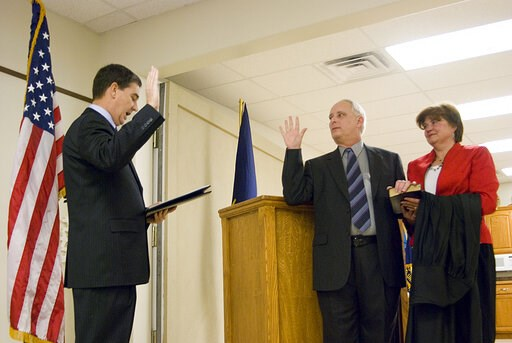 (Estuardo Garcia/The Journal-World via AP). In this Dec. 19, 2008 photo, Michael Gibbens, center, stands next to his wife, Nancy, as he is sworn in as a Leavenworth County District Court judge by District Court Chief Judge David King, left, at the Vete...
