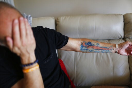 (AP Photo/Brynn Anderson). In this Feb. 5, 2019, photo, Mitch Dworet holds up his arm in Coral Springs, Fla., and talks about the tattoo of his oldest son Nick, a 17-year-old senior with a college swimming scholarship who died in the Marjory Stoneman D...