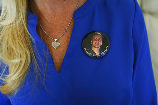 """(AP Photo/Brynn Anderson). In this Tuesday, Feb. 5, 2019, photo, Annika Dworet wears a button with her son Nick's photograph saying """"Forever in our Hearts"""" as she speaks during an Associated Press interview in Coral Springs, Fla. Nick died in the Marjo..."""