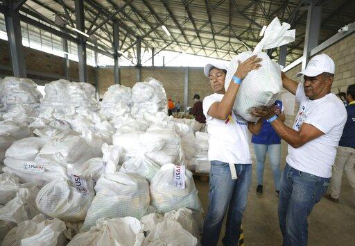 (AP Photo/Fernando Vergara). Venezuelan volunteers place a bag of USAID humanitarian aid for storage at a warehouse next to the Tienditas International Bridge, near Cucuta, Colombia, on the border with Venezuela, Friday, Feb. 8, 2019. Trucks carrying U...