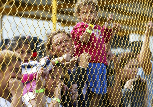 (Jerry Lara/The San Antonio Express-News via AP). Central American immigrant families look out through the fence of a shelter in Piedras Negras, Mexico, Tuesday, Feb. 5, 2019. A caravan of about 1,600 Central American migrants camped Tuesday in the Mex...