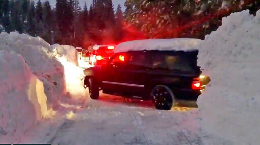 (Joel Keeler via AP). This Wednesday, Feb. 6, 2019 photo from video by Joel Keeler shows vehicles driving through canyons plowed through snow drifts that overshadow them at snowed-in Montecito Sequoia Lodge in Kings Canyon National Park in California's...