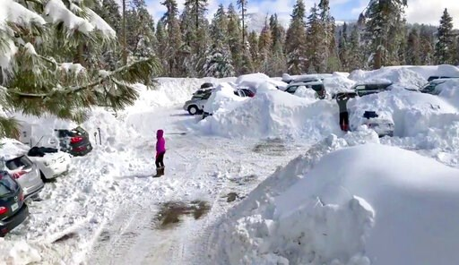 (Joel Keeler via AP). This Wednesday,, Feb. 6, 2019 photo from video by Joel Keeler shows people attempting to clear cars buried in the parking lot of the showed-in Montecito Sequoia Lodge in Kings Canyon National Park in California's Sierra Nevada. Mo...