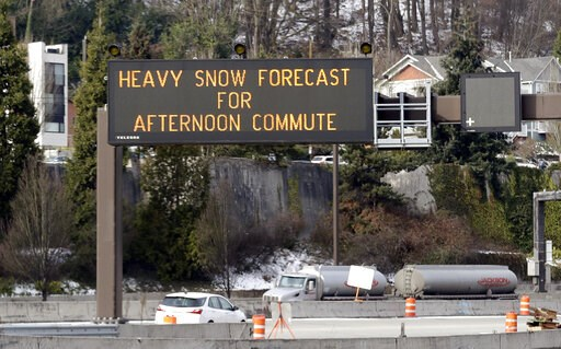 (AP Photo/Elaine Thompson). Light traffic passes by as a highway sign over Interstate 90 warns of expected snow later in the day Friday, Feb. 8, 2019, in Seattle. Officials have issued a winter storm warning for the Puget Sound region including Seattle...