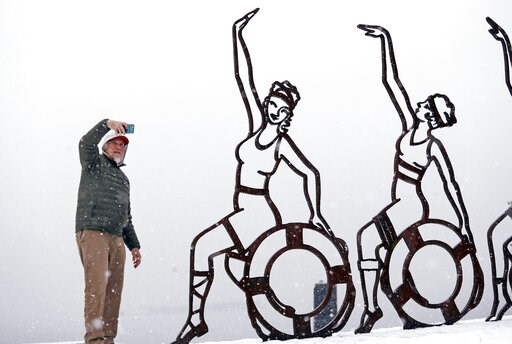 (AP Photo/Elaine Thompson). As the cityscape is lost in a whiteout behind him, Scott Mathews snaps a photo of a metal sculpture of women on a beach during a snowstorm Friday, Feb. 8, 2019, in Seattle. Officials have issued a winter storm warning for th...
