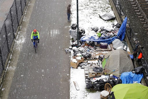 (AP Photo/Elaine Thompson). A bicyclist rides past a homeless encampment as snow falls, Friday, Feb. 8, 2019, in Seattle. Officials have issued a winter storm warning for the Puget Sound region including Seattle.