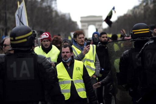 (AP Photo/Kamil Zihnioglu). Yellow vest protesters walk down the famed Champs Elysees avenue to keep pressure on French President Emmanuel Macron's government, for the 13th straight weekend of demonstrations, in Paris, France, Saturday, Feb. 9, 2019.