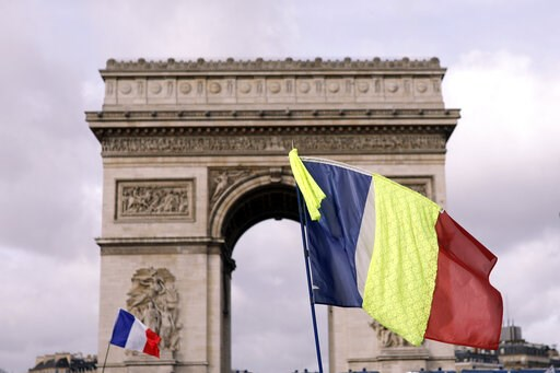 (AP Photo/Kamil Zihnioglu). Yellow vest protesters brandish national flags as they gather around the Arc de Triomphe to keep pressure on French President Emmanuel Macron's government, for the 13th straight weekend of demonstrations, in Paris, France, S...