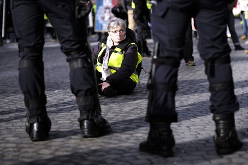 (AP Photo/Kamil Zihnioglu). A woman sits down as other yellow vest protesters gather on the famed Champs Elysees avenue to keep pressure on French President Emmanuel Macron's government, for the 13th straight weekend of demonstrations, in Paris, France...