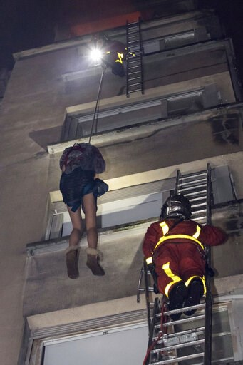(Benoit Moser/BSPP via AP). In this image provided on Tuesday, Feb. 5, 2019 by the Brigade de Sapeurs-Pompiers de Paris (Paris Fire Brigade) firefighters use a rope to evacuate a resident after a fire engulfed an apartment building , in Paris, France. ...