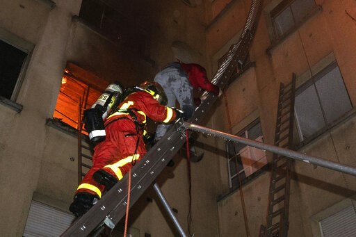 (Benoit Moser/BSPP via AP). In this image provided on Tuesday, Feb. 5, 2019 by the Brigade de Sapeurs-Pompiers de Paris (Paris Fire Brigade) a resident of an apartment building escapes a fire as he is evacuated by a firefighter, in Paris, France. A fir...