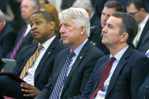 (Bob Brown/Richmond Times-Dispatch via AP). FILE - In this Dec. 18, 2017 file photo, from left, Lt. Governor-elect Justin Fairfax, Attorney General-elect Mark Herring and Governor-elect Ralph Northam listen as Virginia Governor Terry McAuliffe addresse...