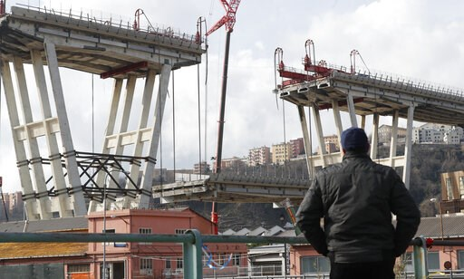 (AP Photo/Antonio Calanni). A man looks the Morandi bridge in Genoa, Italy, Saturday, Feb. 9, 2019. Workers taking apart the remains of a bridge which collapsed in Aug. 2018 are set to remove a 40 meter beam, seen in between the red machinery. A large ...