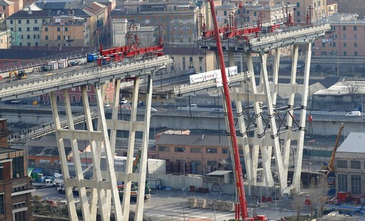 (AP Photo/Antonio Calanni). Cranes lower a section of the Morandi bridge in Genoa, Italy, Saturday, Feb. 9, 2019. Workers taking apart the remains of a bridge which collapsed in Aug. 2018 are set to remove a 40 meter beam, seen in between the red machi...