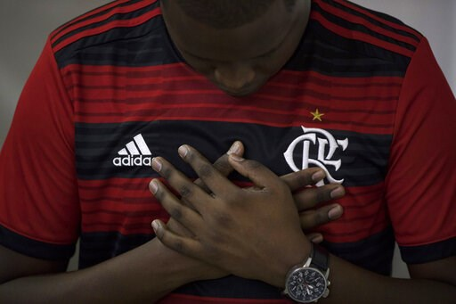 (AP Photo/Leo Correa). A man wearing a Flamengo soccer kit, prays during a memorial Mass for the victims of a fire at a Brazilian soccer academy, in Rio de Janeiro, Brazil, Friday, Feb. 8, 2019. A fire early Friday swept through the sleeping quarters o...