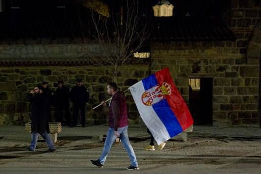 (AP Photo/Visar Kryeziu). A Kosovo Serb protester carries a Serb flag and joins a demonstration against Serbian President Aleksandar Vucic in the town of Gracanica, Kosovo on Saturday, Feb. 9, 2019. Every Saturday thousands of opponents of Serbian pres...