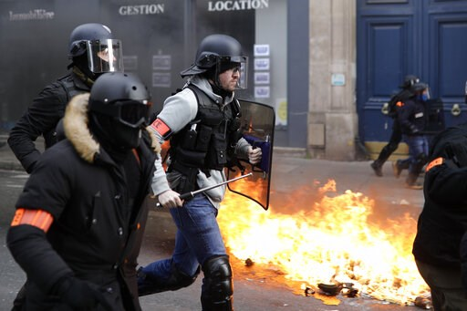 (AP Photo/Kamil Zihnioglu). Riot police run past burning dustbins set on fire by yellow vest protesters as they keep pressure on French President Emmanuel Macron's government, for the 13th straight weekend of demonstrations, in Paris, France, Saturday,...
