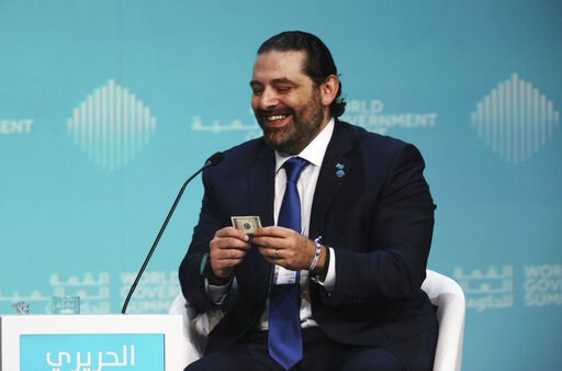 (AP Photo/Jon Gambrell). Lebanese Prime Minister Saad Hariri reacts after receiving a $100 bill from a moderator who said he could keep it if he sold him on investing in Lebanon during the World Government Summit in Dubai, United Arab Emirates, Sunday,...