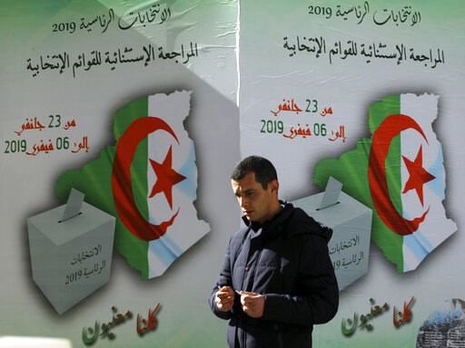 (AP Photo/Anis Belghoul). In this Feb. 5, 2019, photo, a man walks past a poster asking citizen to register to vote in Algiers. More than 180 people want to run for president of Algeria in the April election, amid growing uncertainty about whether Pres...