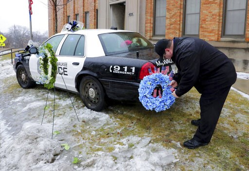 (Mike De Sisti/Milwaukee Journal-Sentinel via AP). Timothy Nelson, of Oak Creek, Wis., places small flags in a bouquet near a squad car adorned with flowers as a memorial for fallen Milwaukee Police Officer Matthew Rittner at the Neighborhood Task Forc...