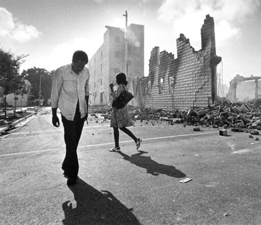 (AP Photo/Kathy Willens, File). FILE - In this May 19, 1980, photo, people walk past ruins in the Culmer section of Miami after rioting over the acquittal of four police officers charged with the 1979 beating death of Arthur McDuffie, a black motorcycl...