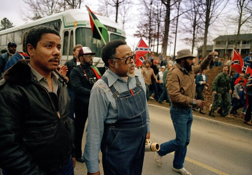 (AP Photo/Gene Blythe). FILE -In this Jan. 18, 1987, photo, Atlanta city councilman, Rev. Hosea Williams, in overalls, leads a march against efforts to keep Forsyth County in Georgia all white past counter-protesters near Cumming, Ga., as a crowd waves...