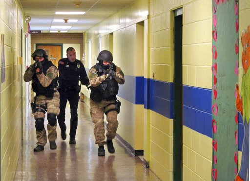 (Omar Ricardo Aquije/The Post-Star via AP, File). FILE - In this Jan. 28, 2013, file photo, members of the Washington County Sheriff's Office and the Hudson Falls Police Department use unloaded guns to take part in an emergency drill as they walk throu...