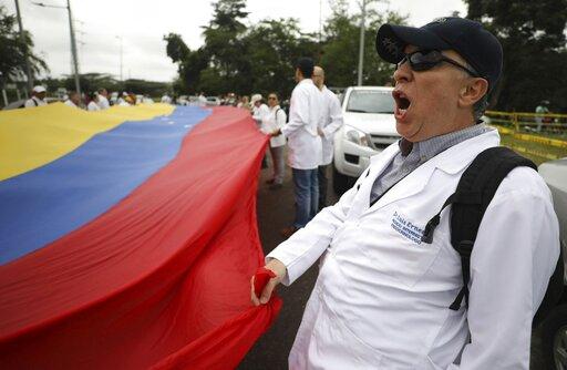 (AP Photo/Fernando Vergara). Venezuelan doctors shout slogans against the government of Venezuela's President Nicolas Maduro at the International Bridge Tienditas, which has been blocked by the Venezuelan military, near Cucuta, Colombia, Sunday, Feb. 1...