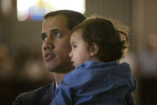 (AP Photo/Rodrigo Abd). Opposition National Assembly President Juan Guaido, who declared himself interim president of Venezuela, holds his daughter Miranda while attending a Mass in a church in Caracas, Venezuela, Sunday, Feb. 10, 2019.