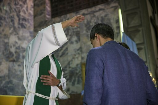 (AP Photo/Rodrigo Abd). National Assembly leader Juan Guaido, who declared himself interim president, receives a blessing from the priest during a Mass at a church in Caracas, Venezuela, Sunday, Feb. 10, 2019.