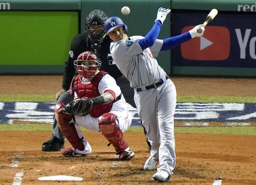 (AP Photo/Elise Amendola, File). FILE - In this Oct. 24, 2018, file photo, Los Angeles Dodgers' Manny Machado, right, hits a single in front of Boston Red Sox catcher Christian Vazquez during the fourth inning in Game 2 of the World Series baseball gam...
