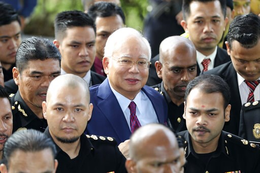 (AP Photo/Vincent Thian, File). FILE - In this July 4, 2018, file photo, former Malaysian Prime Minister Najib Razak, center, arrives at a court house in Kuala Lumpur, Malaysia. Najib is hardly lying low ahead of his corruption trial set to begin Tuesd...