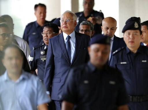 (AP Photo/Vincent Thian, File). FILE - In this Oct. 4, 2018, file photo, former Malaysian Prime Minister Najib Razak, center, walks out of courtroom at Kuala Lumpur High Court in Kuala Lumpur, Malaysia. Najib is hardly lying low ahead of his corruption...