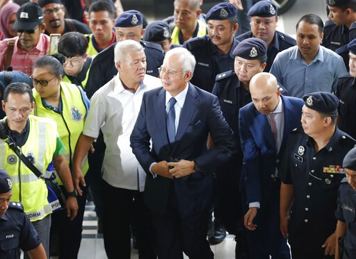 (AP Photo/Vincent Thian, File). FILE - In this Oct. 4, 2018, file photo, former Malaysian Prime Minister Najib Razak, center, arrives at Kuala Lumpur High Court in Kuala Lumpur, Malaysia. Najib is hardly lying low ahead of his corruption trial set to b...